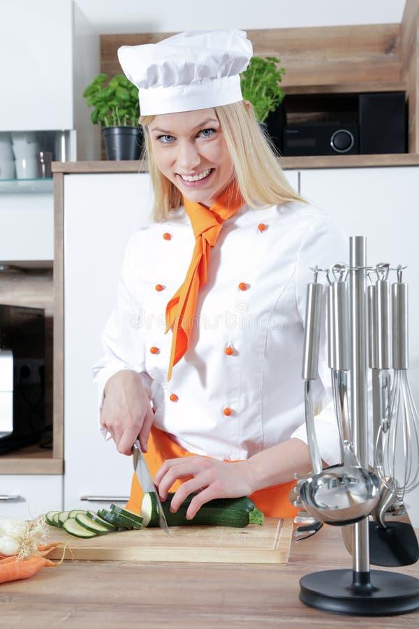 El cocinero de sexo femenino hermoso joven está cocinando en una cocina un poco de comida con la carne de las verduras foto de archivo