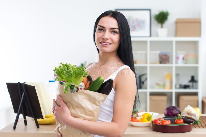 El cocinero de sexo femenino que sostenía el bolso lleno de verdes, acaba de volverse de mercado, alista para preparar la comida  fotos de archivo