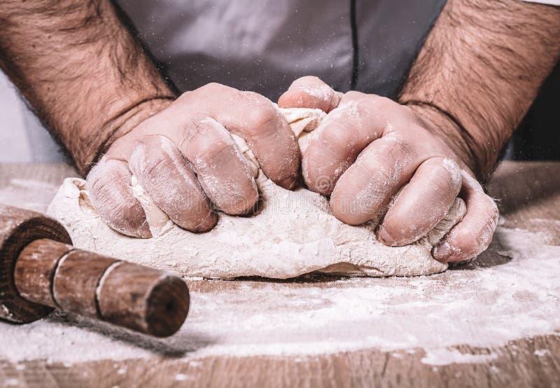 El cocinero de sexo masculino amasa la pasta foto de archivo