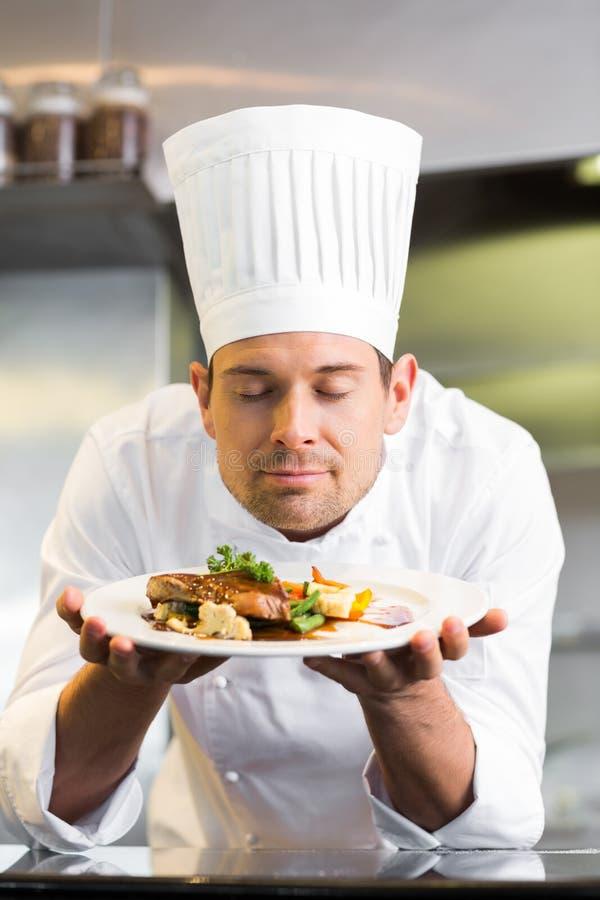 El cocinero de sexo masculino con los ojos cerró la comida que olía en cocina imagen de archivo