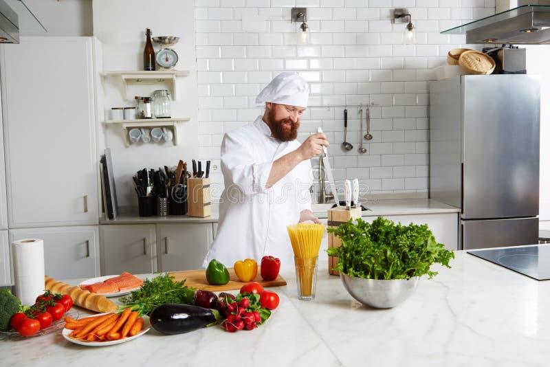 El cocinero de sexo masculino sonriente prepara su cocina para que comenzó cocine fotografía de archivo libre de regalías