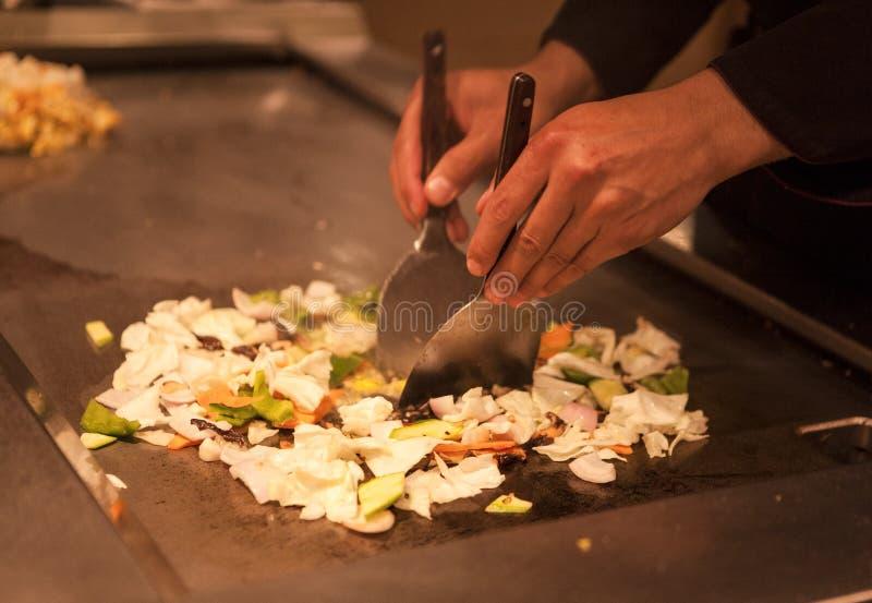El cocinero del chino prepara la carne de vaca frita y verduras del plato picante Los cocineros de las manos preparan el primer c fotografía de archivo libre de regalías
