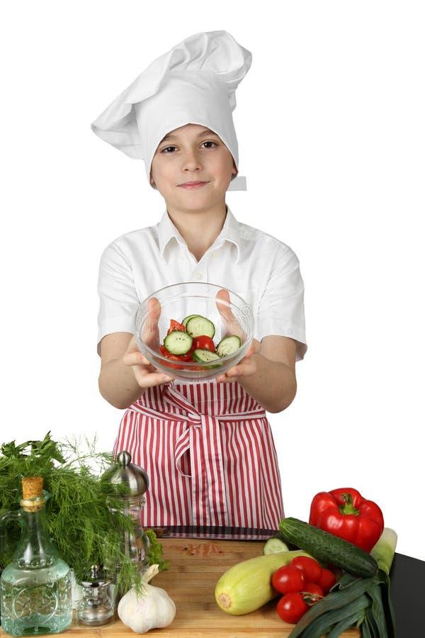 El cocinero del niño pequeño sostiene el cuenco de ensalada imagen de archivo libre de regalías