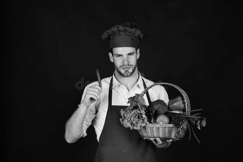 El cocinero en el uniforme de Borgoña sostiene el chile rojo disponible imagen de archivo libre de regalías