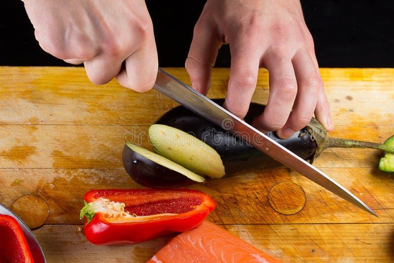 El cocinero está cortando la berenjena fotografía de archivo