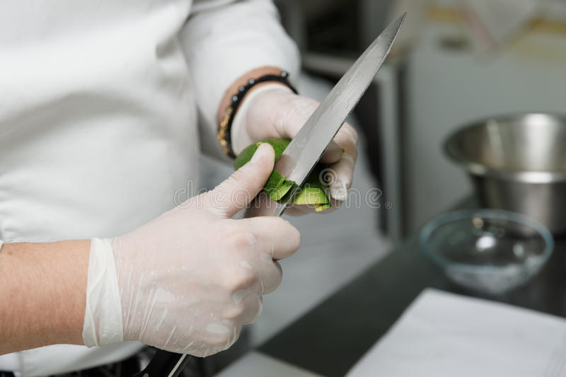 El cocinero está pelando el aguacate imagen de archivo