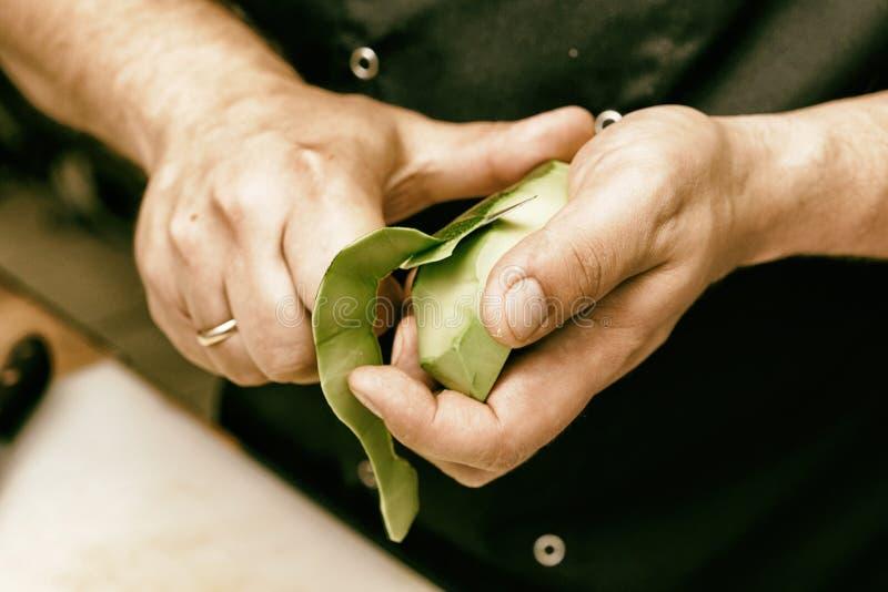 El cocinero está pelando el aguacate, entonado fotografía de archivo libre de regalías