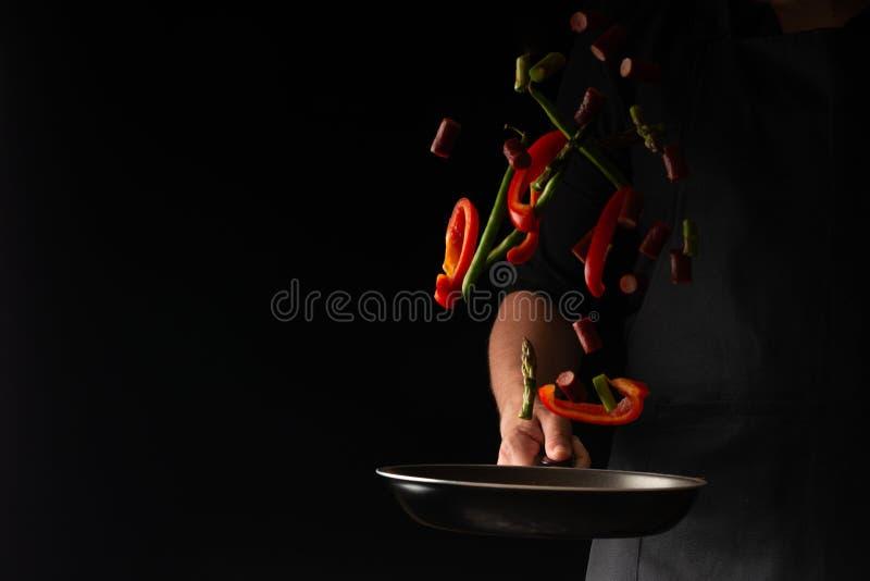 El cocinero est? cocinando las salchichas de los salchichones con pimienta dulce y habas spriykovoy, en un fondo negro, un libro  fotos de archivo