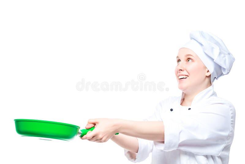 el cocinero experimentado lanza para arriba la comida en una cacerola, retrato emocional en un fondo blanco fotos de archivo