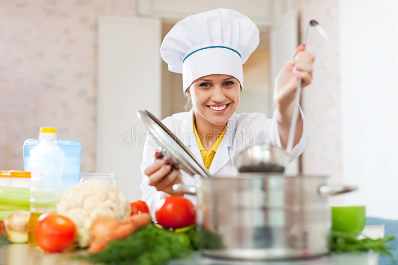 El cocinero feliz trabaja con la cucharón en la cocina fotos de archivo