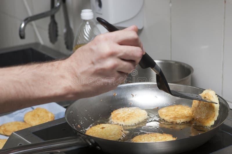 El cocinero fríe las crepes de patata foto de archivo