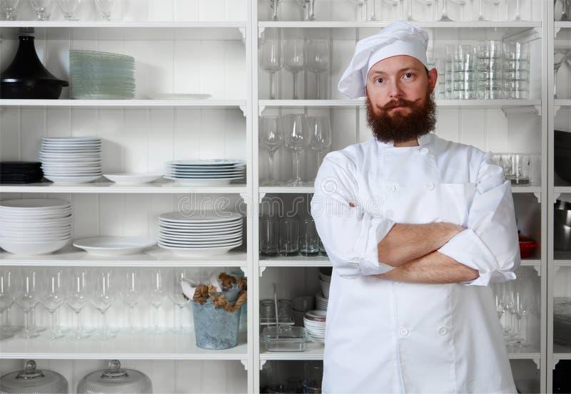 El cocinero hermoso del hombre que se colocaba con sus brazos cruzó contra un gabinete blanco con los platos foto de archivo libre de regalías