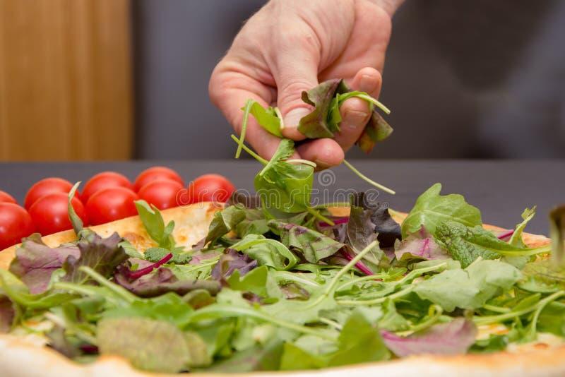 El cocinero lanza la pizza con las rebanadas de lechuga y de hierbas frescas, el cocinar de la pizza imagenes de archivo