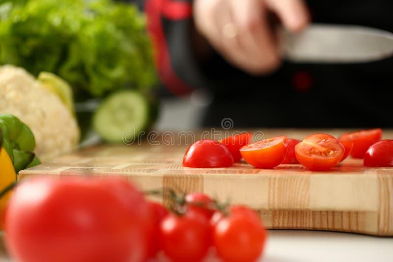 El cocinero lleva a cabo el cuchillo a disposición y cortes encendido imagenes de archivo