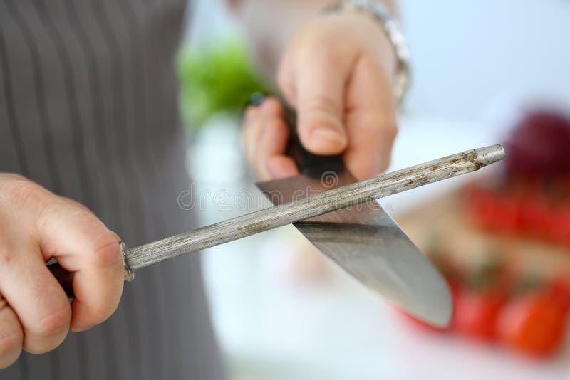 El cocinero lleva a cabo número y el musat en su mano imagen de archivo