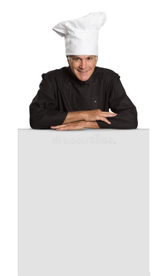 El cocinero maduro del hombre en pulgares uniformes sube y mostrando visitar en blanco fotografía de archivo