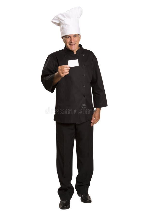 El cocinero maduro del hombre en pulgares uniformes sube y mostrando visitar en blanco fotografía de archivo libre de regalías