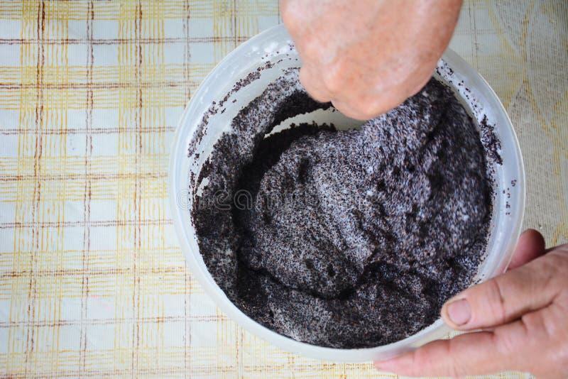 El cocinero mezcla las claras de huevo con las semillas de amapola para preparar una torta fotos de archivo
