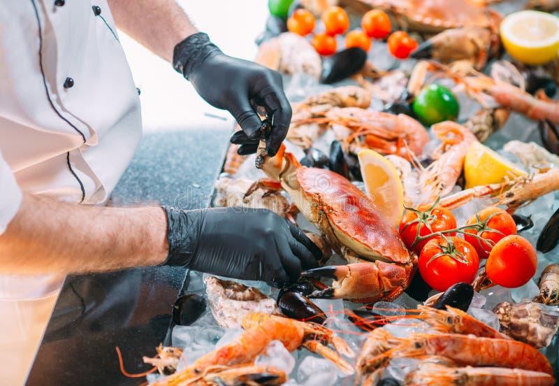 El cocinero pone los mariscos en una bandeja en el restaurante fotografía de archivo