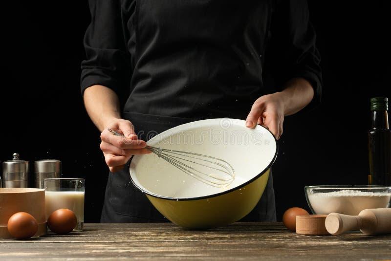 El cocinero prepara la pasta para el pan, la pizza y los dulces El concepto de comida En un fondo negro, congelando en el movimie imagen de archivo