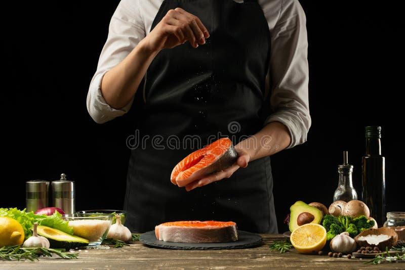 El cocinero prepara los pescados de color salmón frescos, trucha de Crumbu, asperja la sal del mar con los ingredientes Preparaci fotos de archivo libres de regalías