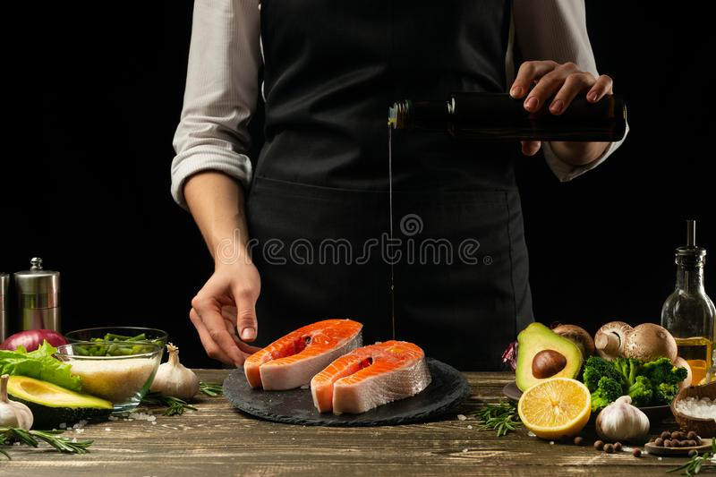 El cocinero prepara salmones, la trucha, el agua con aceite de oliva y verduras de los pescados frescos Foto horizontal El cocina imagen de archivo