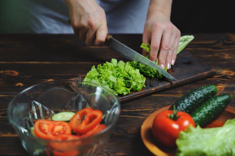 El cocinero prepara una ensalada de verduras imagen de archivo