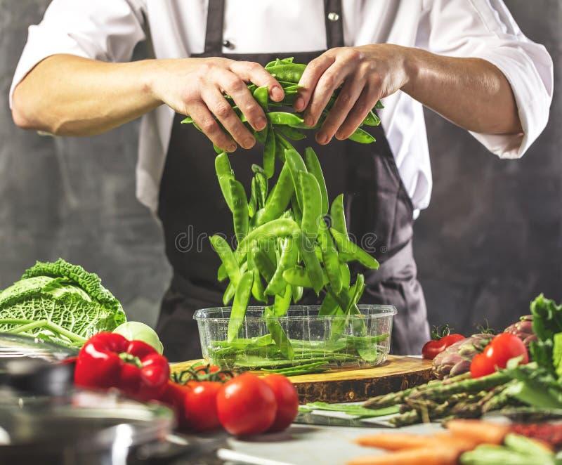 El cocinero prepara verduras para cocinar en la cocina del restaurante imagen de archivo libre de regalías