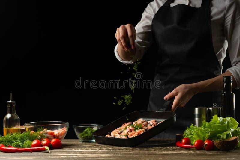 El cocinero profesional asperja los camarones para la ensalada, los mariscos y el concepto sano de la comida Foto horizontal, men imagen de archivo