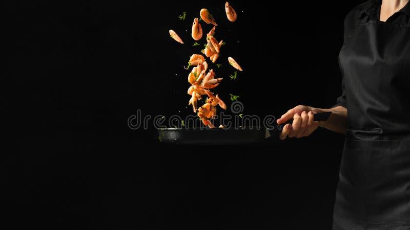 El cocinero profesional prepara camarones con verdes Cocinar los mariscos, la comida vegetariana sana, y la comida en un fondo os imagenes de archivo