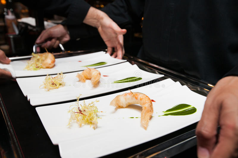 El cocinero puso la comida en la bandeja antes de servido por el camarero imagen de archivo