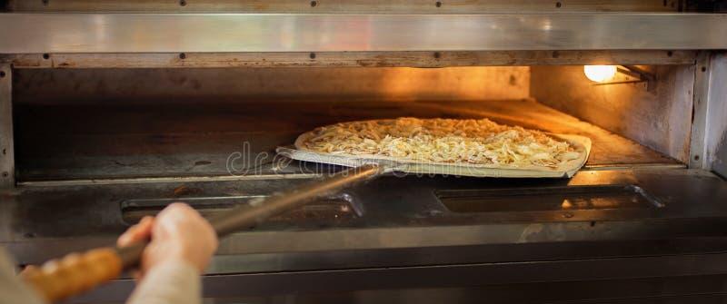 El cocinero puso la pizza cruda deliciosa a la estufa para la pizza cocida foto de archivo