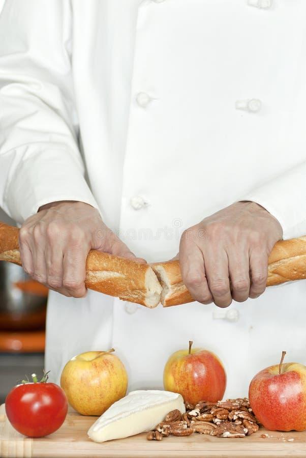 El cocinero rompe el Baguette fotografía de archivo libre de regalías