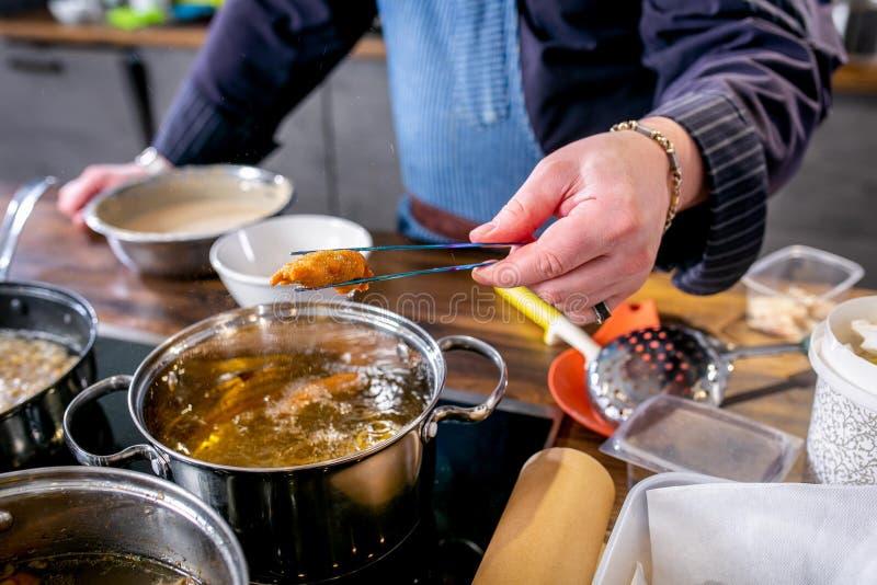 El cocinero saca pedazos fritos de los pescados en talud Clase principal en la cocina El proceso de cocinar Paso a paso preceptor fotografía de archivo libre de regalías