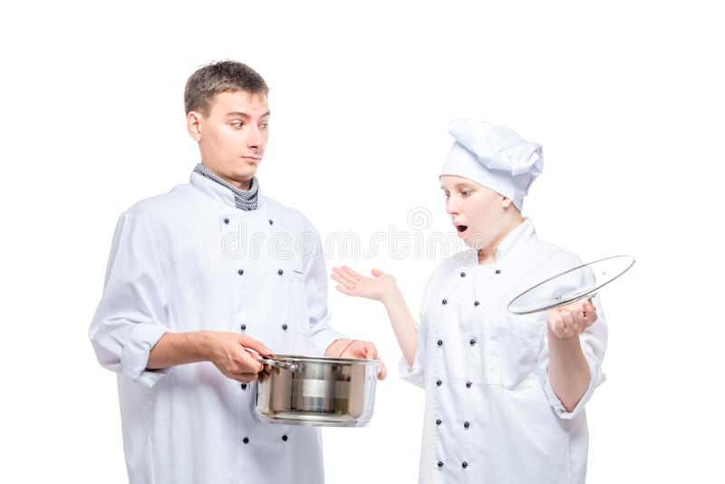 el cocinero sorprendido mira la sopa en una cacerola de otro cocinero en un blanco fotos de archivo