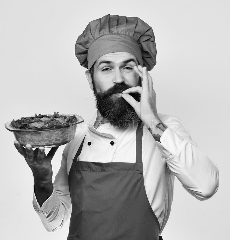 El cocinero sostiene el cuenco con la cazuela de la patata que muestra la muestra sabrosa estupenda Cocinero con la cara feliz en imágenes de archivo libres de regalías