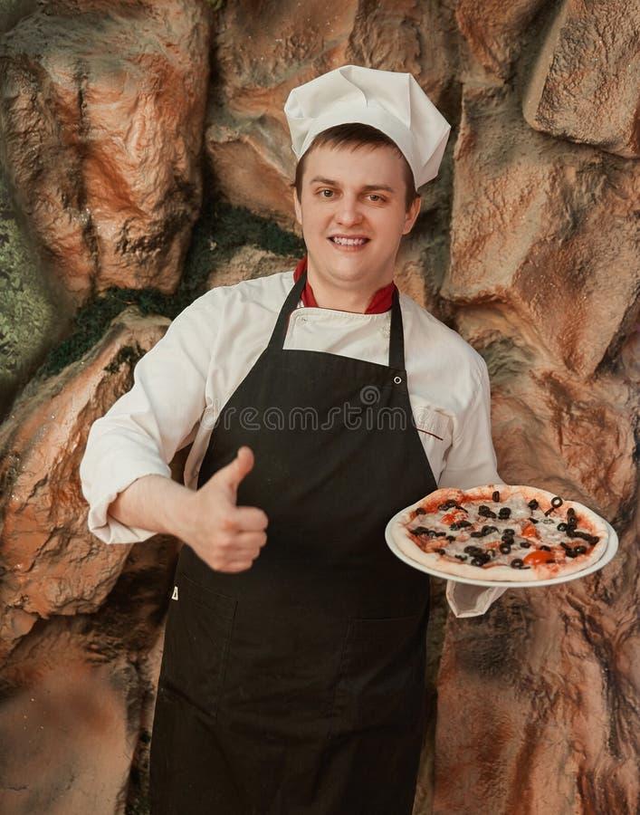 El cocinero sostiene una pizza grande y muestra un pulgar para arriba fotos de archivo libres de regalías
