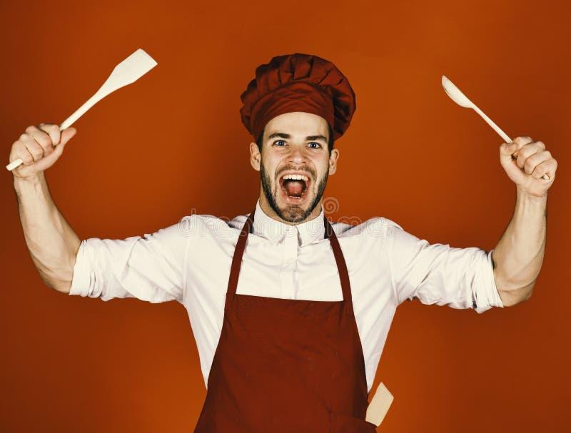 El cocinero trabaja en cocina El cocinero con la cara emocionada sostiene la cuchara y la espátula de madera en fondo rojo Artícu imagen de archivo
