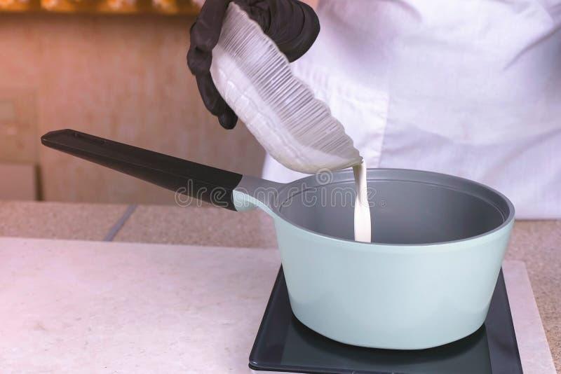 El cocinero vierte la crema del cuenco en el cazo para recalentar Manos en primer de goma negro de los guantes imagen de archivo libre de regalías