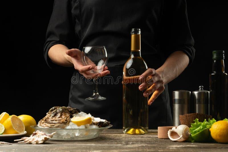 El cocinero vierte, prueba el vino seco italiano con las ostras con el limón en un fondo negro, el concepto de mariscos, vino, me fotos de archivo libres de regalías