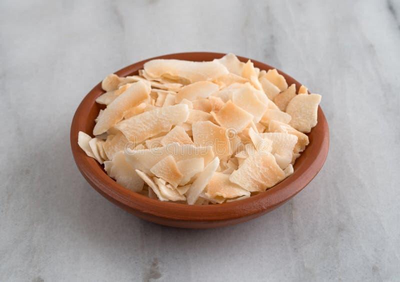 El coco tostado forma escamas en un cuenco en una encimera fotos de archivo libres de regalías