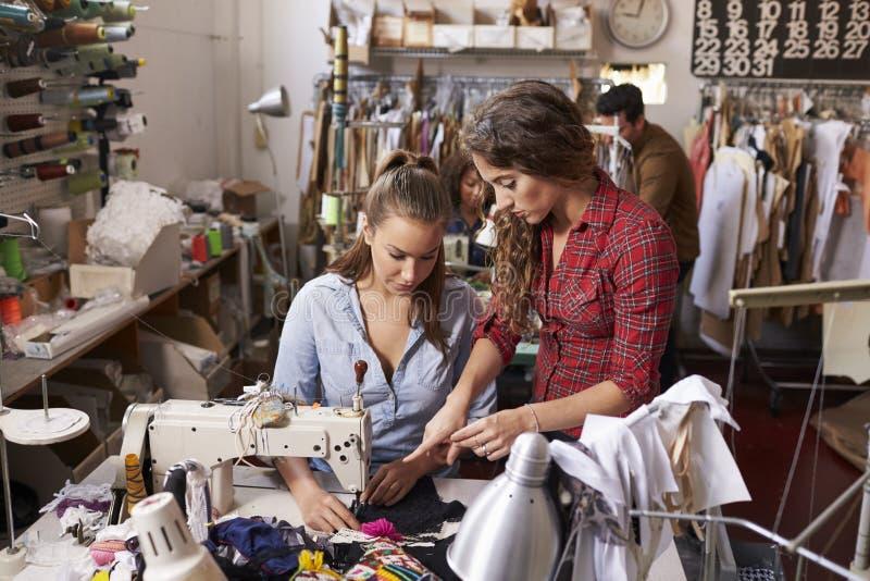 El colega aconseja al maquinista del aprendiz en el estudio del diseño de la ropa fotos de archivo
