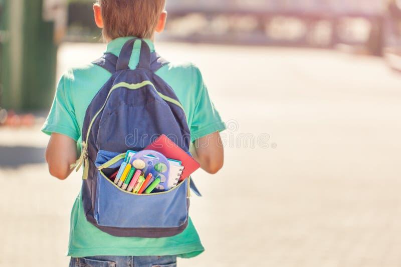 El colegial con la mochila llena va a la escuela Visión posterior imagen de archivo