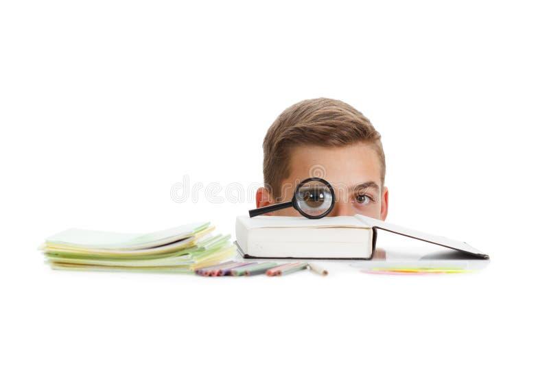 El colegial de la diversión se sienta cerca del escritorio con las fuentes de escuela aisladas en blanco fotos de archivo