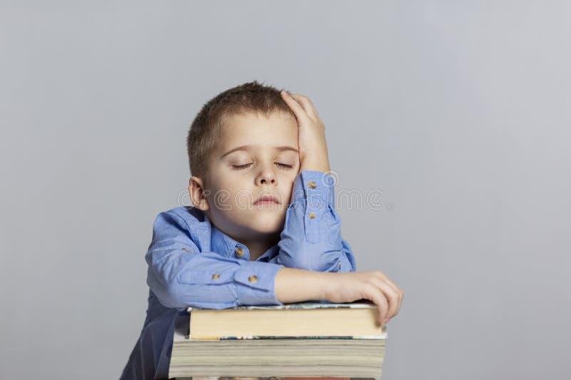 El colegial lindo duerme en una pila de libros Primer Fondo gris imagenes de archivo
