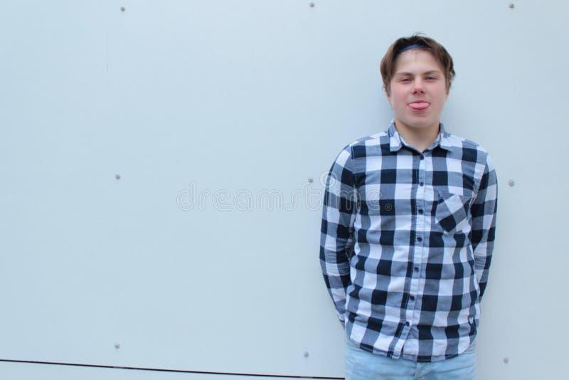 El colegial o el estudiante del adolescente del muchacho se está colocando en las escaleras en una camisa, sonriendo, mochila roj fotografía de archivo
