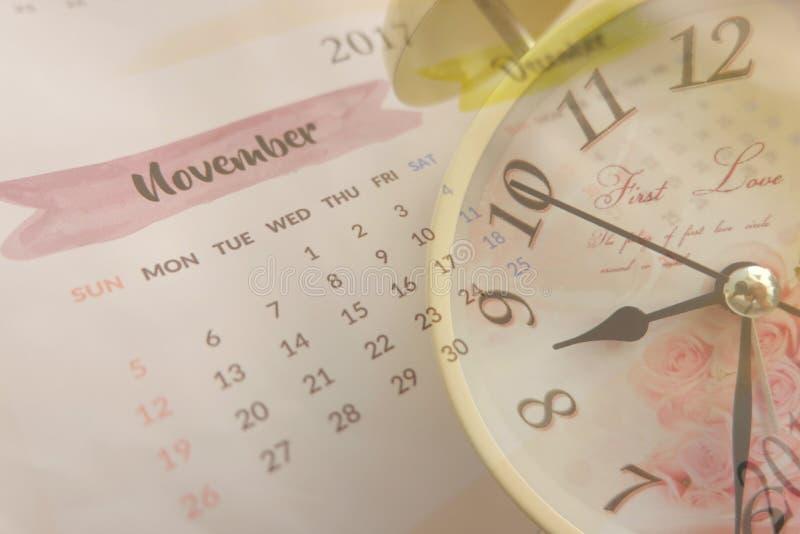 el collage con el reloj del vintage y el calendario paginan en noviembre de 2017 imagenes de archivo