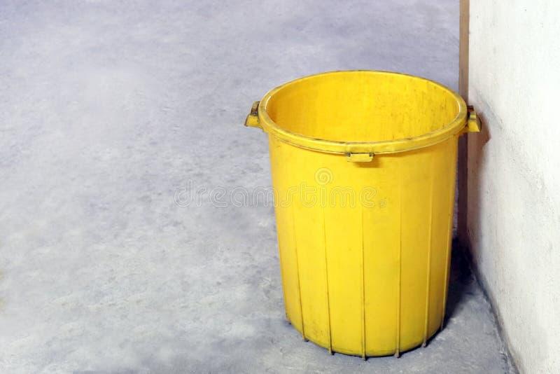 El color amarillo plástico del compartimiento viejo para la descarga inútil, compartimiento vacío para la basura de la basura en  imagen de archivo libre de regalías