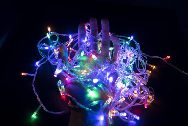 El color de la luz que destella en la mano que sostiene los BU ligeros foto de archivo libre de regalías
