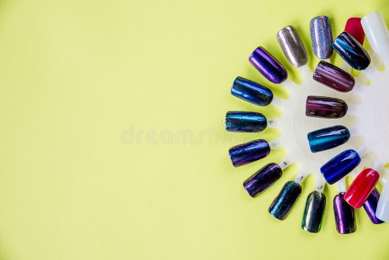 El color del polaco para la manicura Diseño para los clavos esmalte de uñas de los probadores Manicura de la moda en fondo amaril imagen de archivo libre de regalías